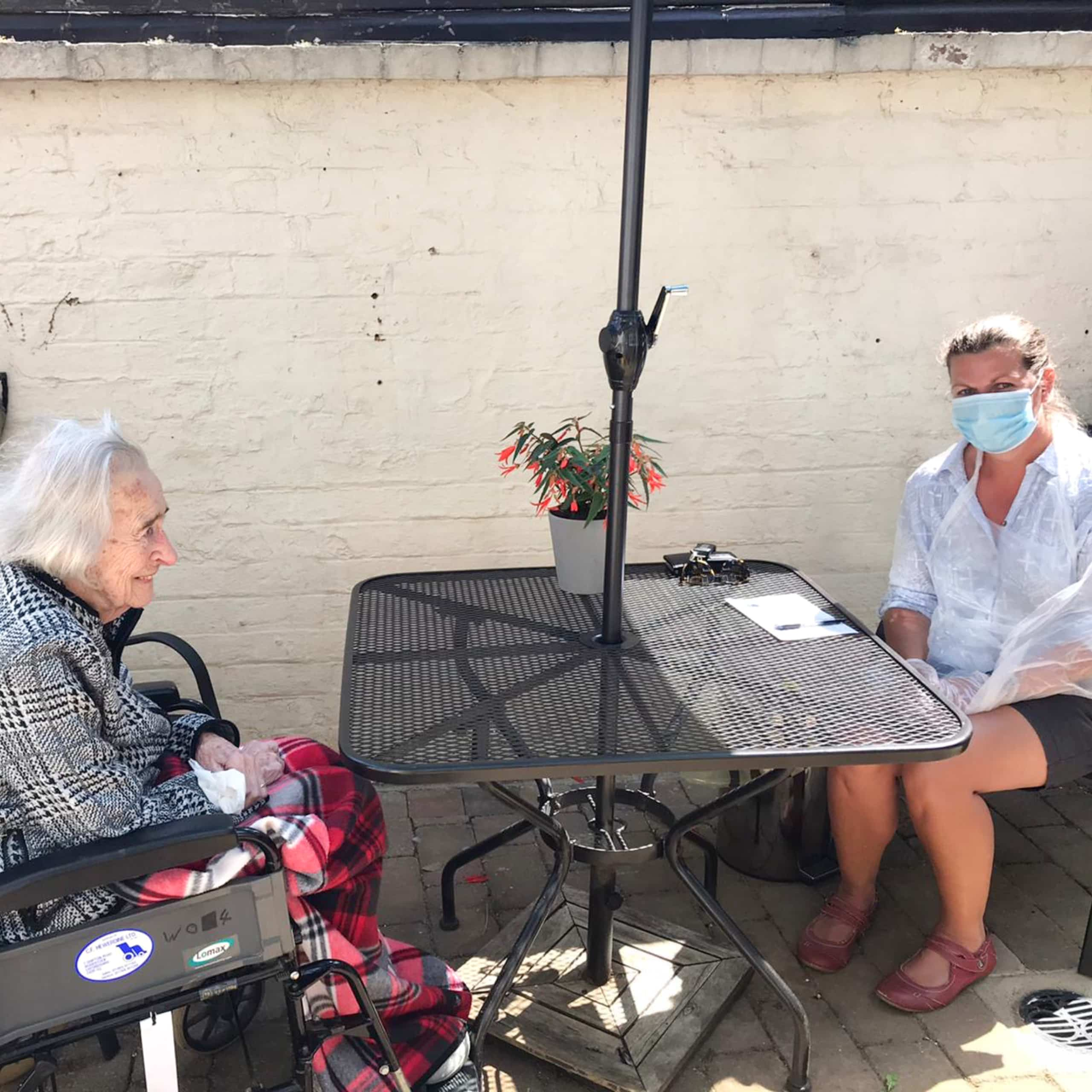 A resident and her relative in the safe outside visiting area at Featherton House Care Home in Deddington.