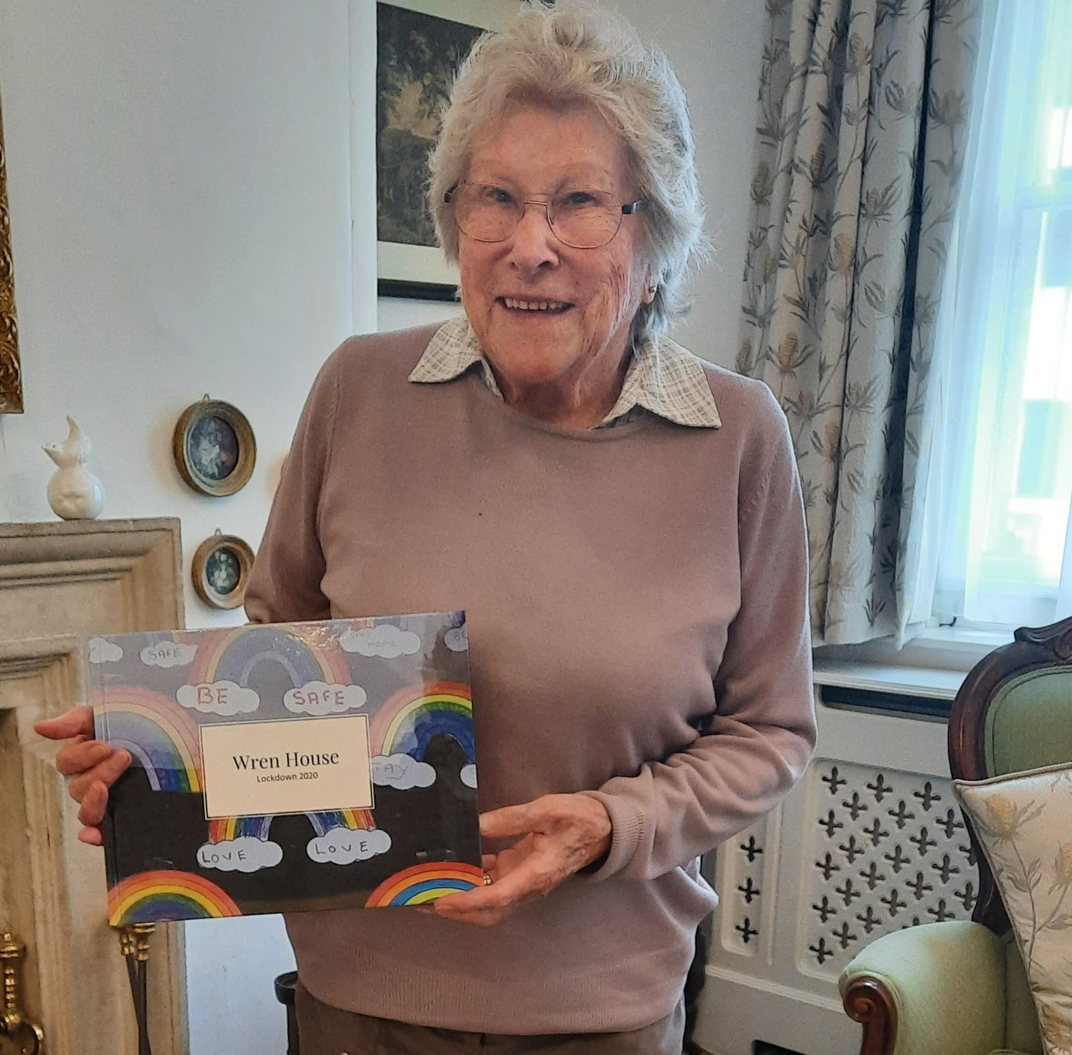 Wren House resident Pauline Taylor holding the Wren House book.