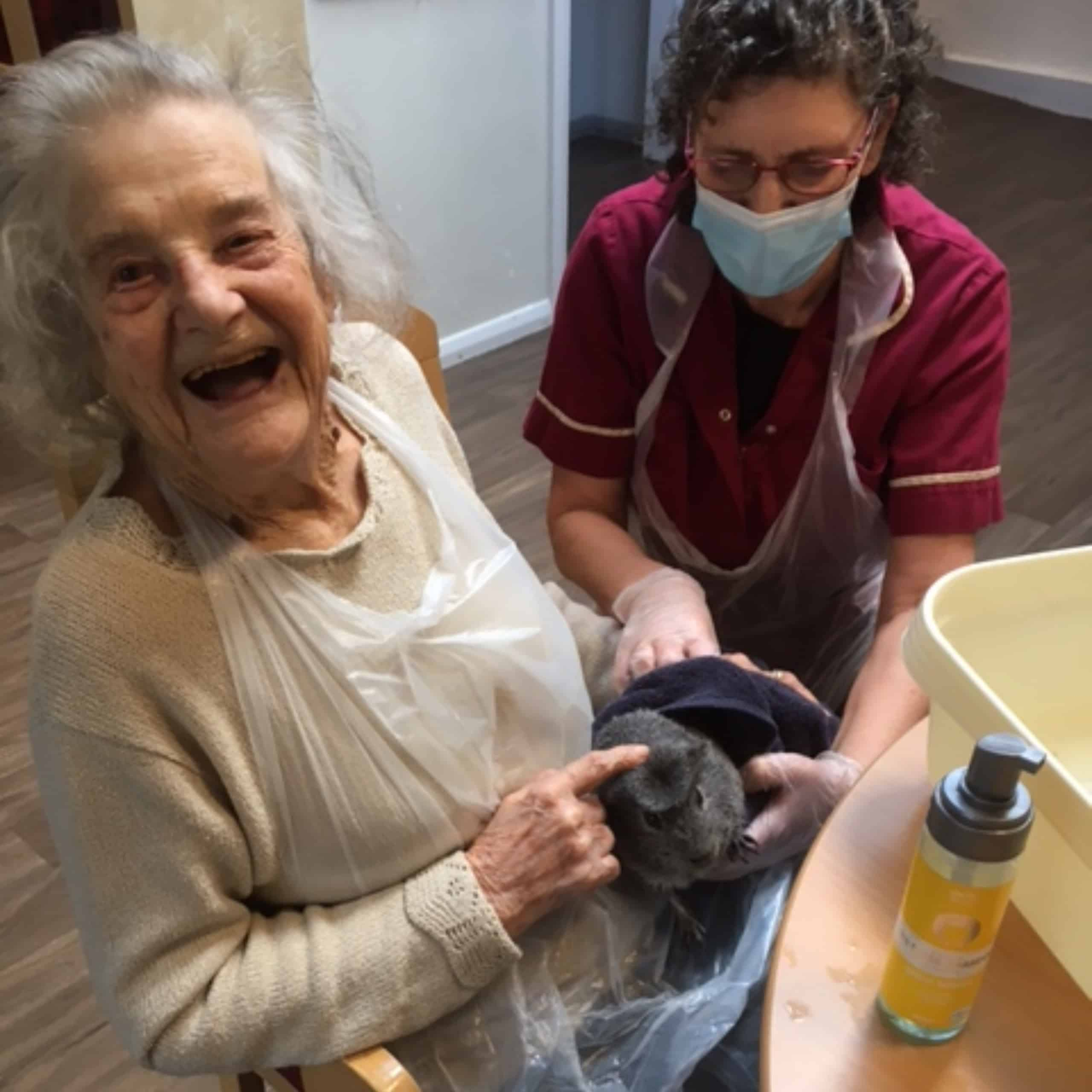 Linden House resident Joan enjoying spending time with one of the Epsom care home's pet guinea pigs.