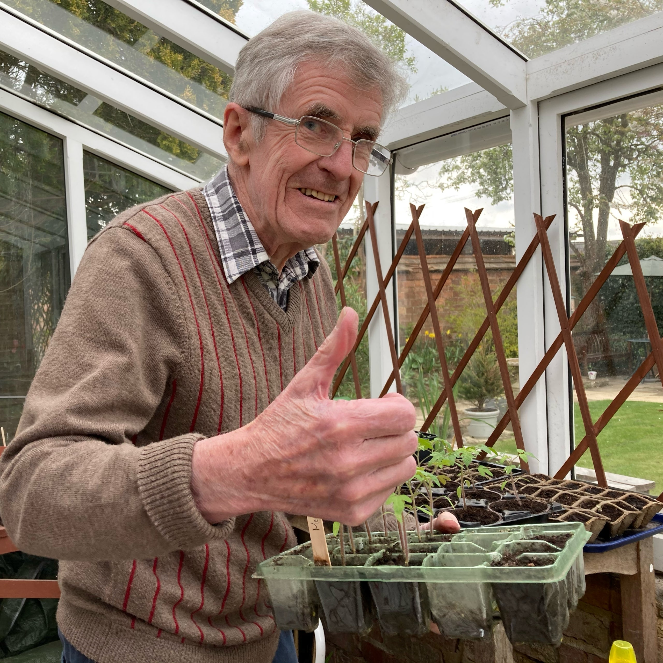 Jock Pirie, resident of Oxfordshire care home Featherton House, with a tray of seedlings in the home's rejuvenated greenhouse.